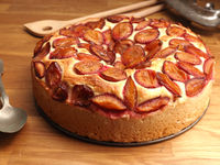 Delicious plum cake made from organic ingredients in a baking plate on a rustic kitchen table