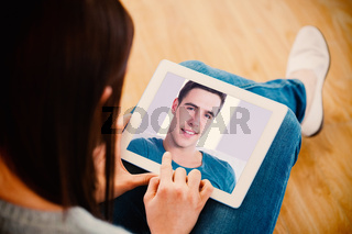 Composite image of smiling handsome man relaxing on couch using tablet