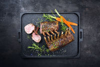 Barbecue rack of lamb with carrot and herbs offered as top view on a modern design cast iron tray with copy space