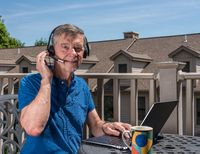Senior man working from home on outdoor deck with headset and computer