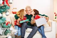 Kinder küssen Opa auf Wange zu Weihnachten