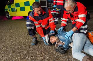 Paramedics helping motorbike driver lying on road