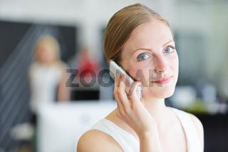 Junge Frau telefoniert mit Smartphone im Büro
