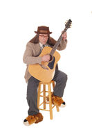 Happy musician playing guitar in a brown jacket and hat