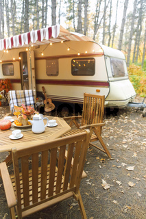 Table and chairs outside trailer in nature