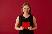 Smiling woman holding sparkling heart on red background