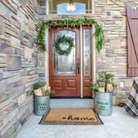 Square frame Front door to a house decorated with green wreath