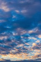 Beautiful clouds in blue sky, illuminated by rays of sun at colorful sunset to change weather. Abstract meteorology background