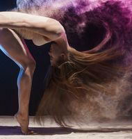 Graceful female gymnast in cloud of color dust