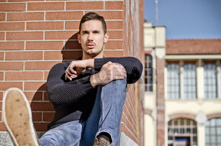 Attractive, confident young man sitting against brick wall