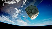 old soccer ball in space on Earth orbit
