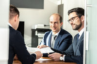 Group of confident successful business people reviewing and signing a contract to seal the deal at business meeting in modern corporate office.