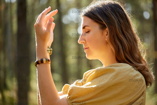 woman or witch performing magic ritual in forest