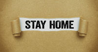Torn paper revealing the words Stay home