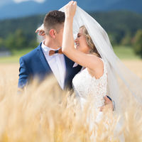 Groom hugs bride tenderly while wind blows her veil in wheat field somewhere in Slovenian countryside.