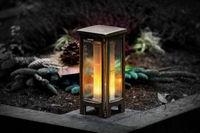 Grablaterne mit brennender Kerze bei Nacht