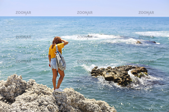Female tourist wanderlust with backpack wearing sunglasses and straw hat during summer trip