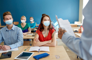 group of students in masks and teacher at school