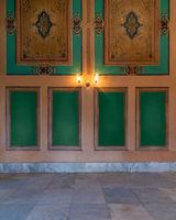 Elegant carved green frames on orange wall with ornate border and lanterns over marble floor