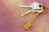 Three old house keys on keyring over grunge background