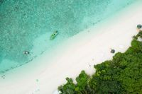 Aerial drone view of picture perfect beach and turquoise lagoon on small tropical island on Maldives