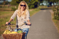 Happy woman riding a bicycle in the countryside