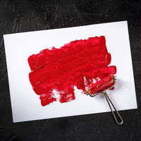 Red paint background with a roller, an abstract texture with a place for text, square overhead shot