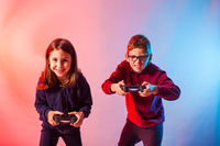 Excited kids with joysticks playing an interesting virtual game