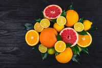citrus fruits, half grapefruits, lemons, oranges, limes with green leaves lie on a brown wooden table. view from above