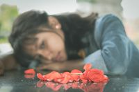Selective focus on red rose lonely young teenager - concept of love breakup or broken heart.
