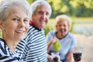 Senioren Rentner Gruppe trinkt ein Glas Rotwein