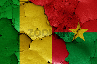 flags of Mali and Burkina Faso painted on cracked wall
