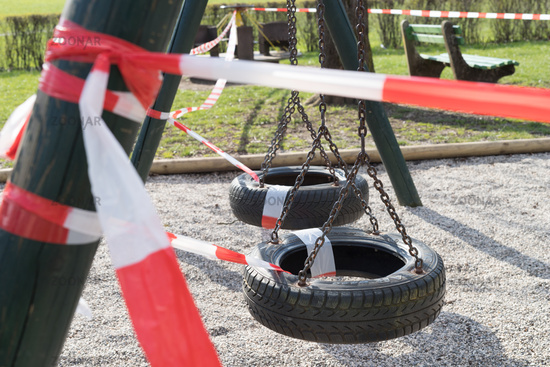 Corona virus COVID-19 restriction. No people due to quarantine. Closed urban park. Empty park and playground. Stay at home compaign. Red warning tape on ramps and slides. Social distancing