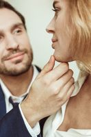 Close up portrait of passionate couple looking each other. Man touching female face. Selective focus on male hand and sexy blonde profile in foreground