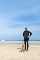 Senior man sporting with dog at beach