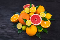 citrus fruits, half grapefruits, lemons, oranges, limes with green leaves lie on a brown wooden table
