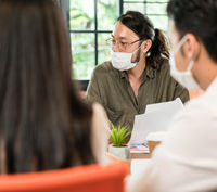 Business person brainstorm in meeting room with face mask.