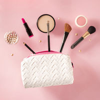 Professional makeup, flying out of a bag, on a pink background. Lipstick, brushes, powder compact, a creative beauty design, square image