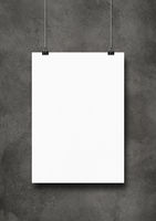 White poster hanging on a dark concrete wall with clips