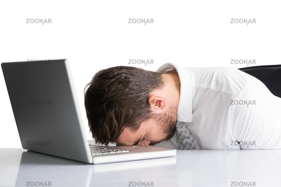 Exhausted businessman sleeping head on laptop