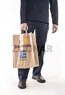 Mann mit Papiertüte von Edeka