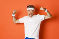 Image of funny middle-aged sportsman in white headband and t-shirt, flexing biceps to show-off, standing against orange background