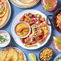 Mexican food, a flat lay. Nachos, tortillas, Paloma cocktails and other dishes, overhead square shot