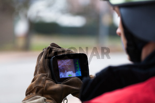 Feuerwehrmann mit Waermebild Kamera