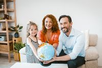 Smiling parents and daughter holding globe, planning vacation.