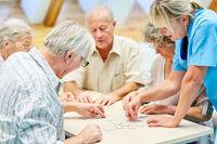 Gruppe Senioren mit Puzzle im Seniorenheim beim Spielen