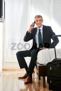 Geschäftsmann im Hotel telefoniert mit Smartphone