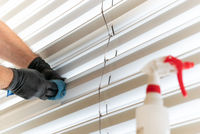 caucasian man cleaning professionally cleaning window blinds with a micro fiber cloth and cleaning detergent