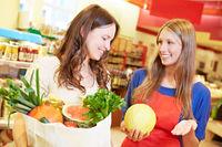 Verkäuferin empfiehlt Kundin eine Honigmelone