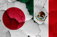 flags of Japan and Mexico painted on cracked wall